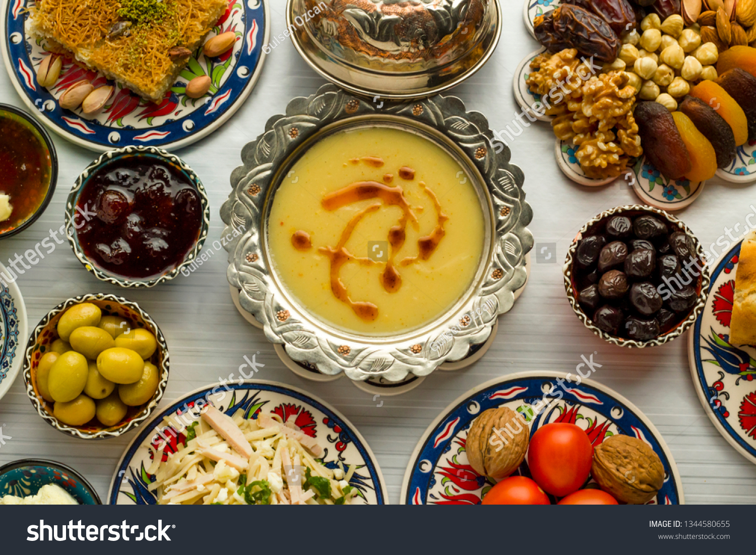 Traditional Turkish Ramadan,iftar meal table with lentil soup on the middle of table with other foods.Used Traditional Turkish Ceramic utensils and copper soup bowl together.