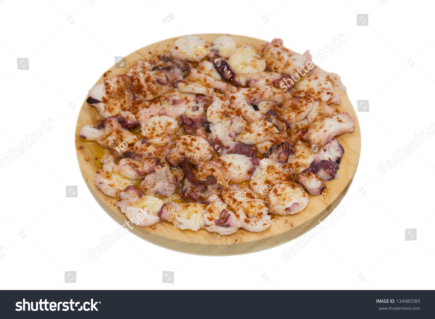 cooked octopus slices dressed with paprika over wooden plate and white ...