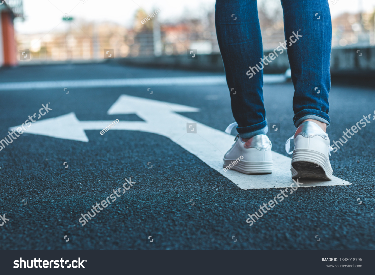 Make decision which way to go. Walking on directional sign on asphalt road. Female legs wearing jeans and white sneakers. #1348018796