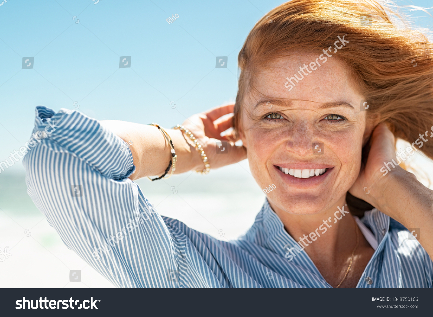Portrait of beautiful mature woman with wind fluttering hair. Closeup face of healthy young woman with freckles looking at camera. Lady with red hair standing at seaside enjoying breeze at beach. #1348750166