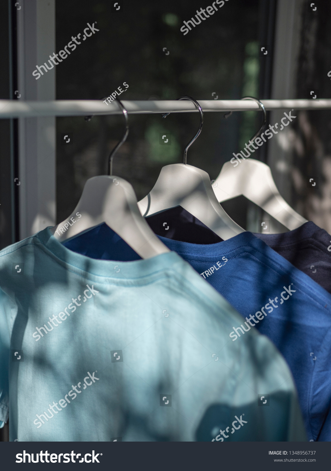 Blue and navy blue t-shirts on hangers, close up view  #1348956737