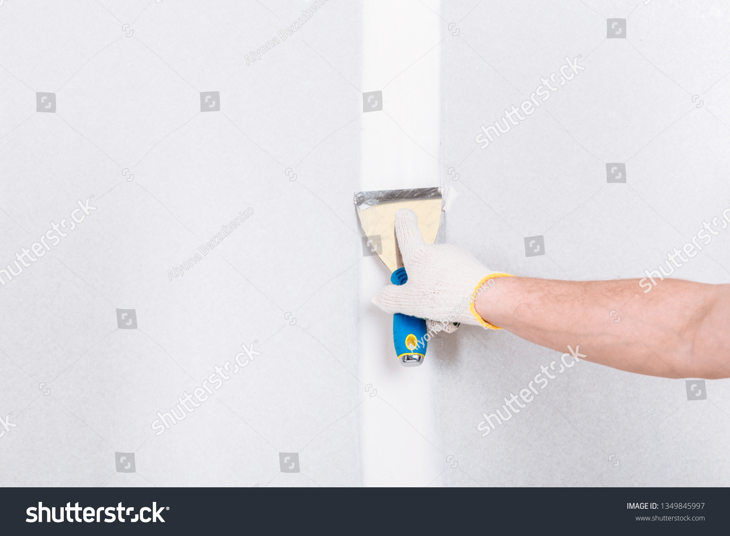 Man with putty knife shows how to hide the connection place between two pieces of dry walls using putty and construction tape #1349845997