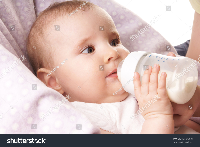 pretty baby girl drinking milk bottle stock photo (100% legal