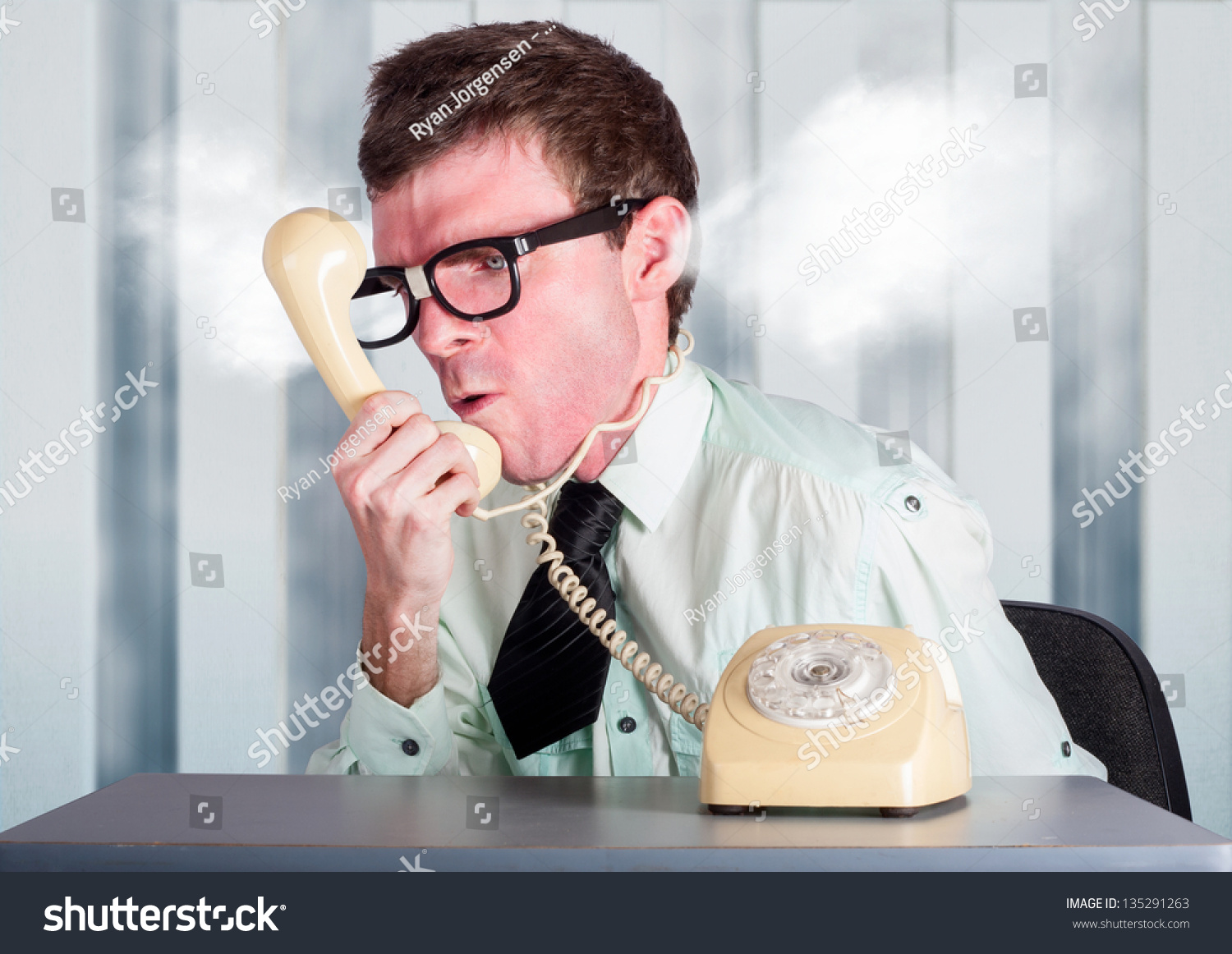 Frustrated office worker on the phone holding stock photo image - Steaming Angry Nerd Businessman Holding Retro Phone Cord Around Big Red Head While Shouting Out Demands