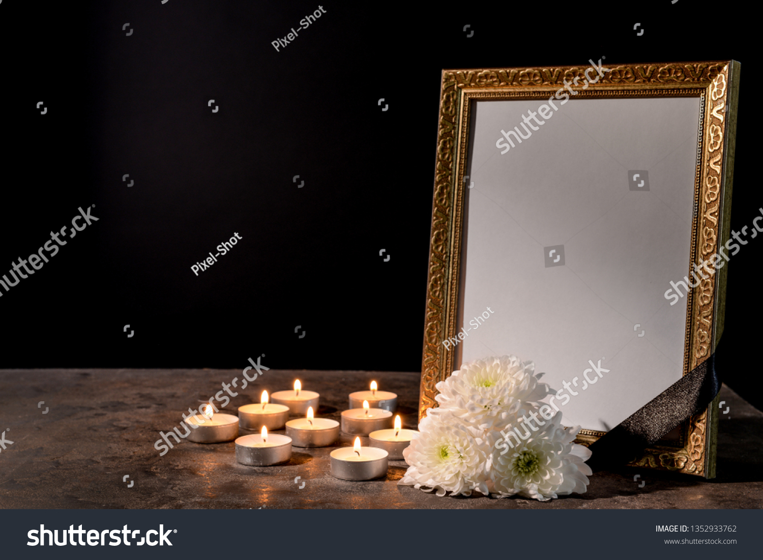 Blank funeral frame, candles and flowers on table against black background #1352933762