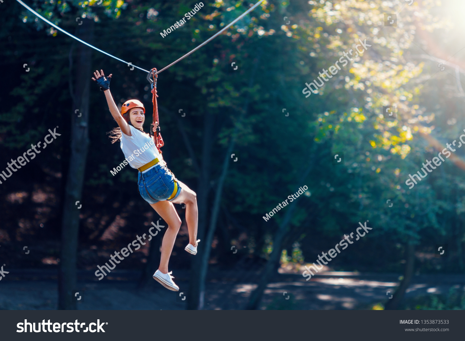 Happy women girl female gliding climbing in extreme road trolley zipline in forest on carabiner safety link on tree to tree top rope adventure park. Family weekend children kids activities concept #1353873533