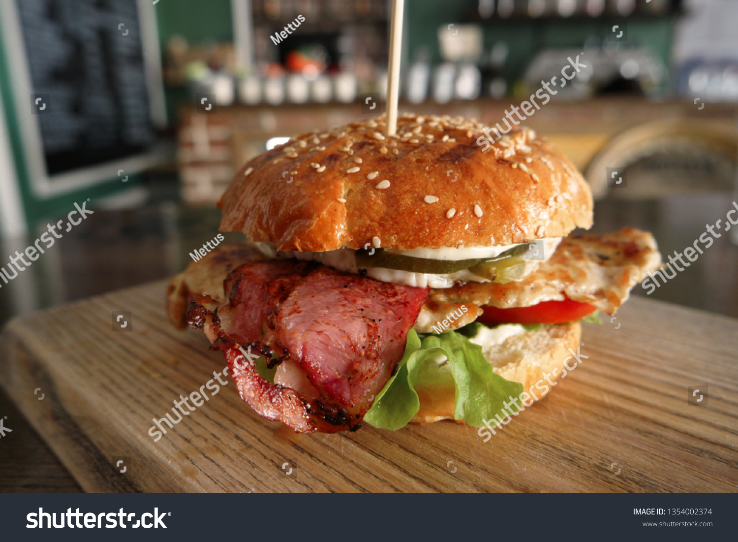 Grilled burger served on wooden board on table in pub