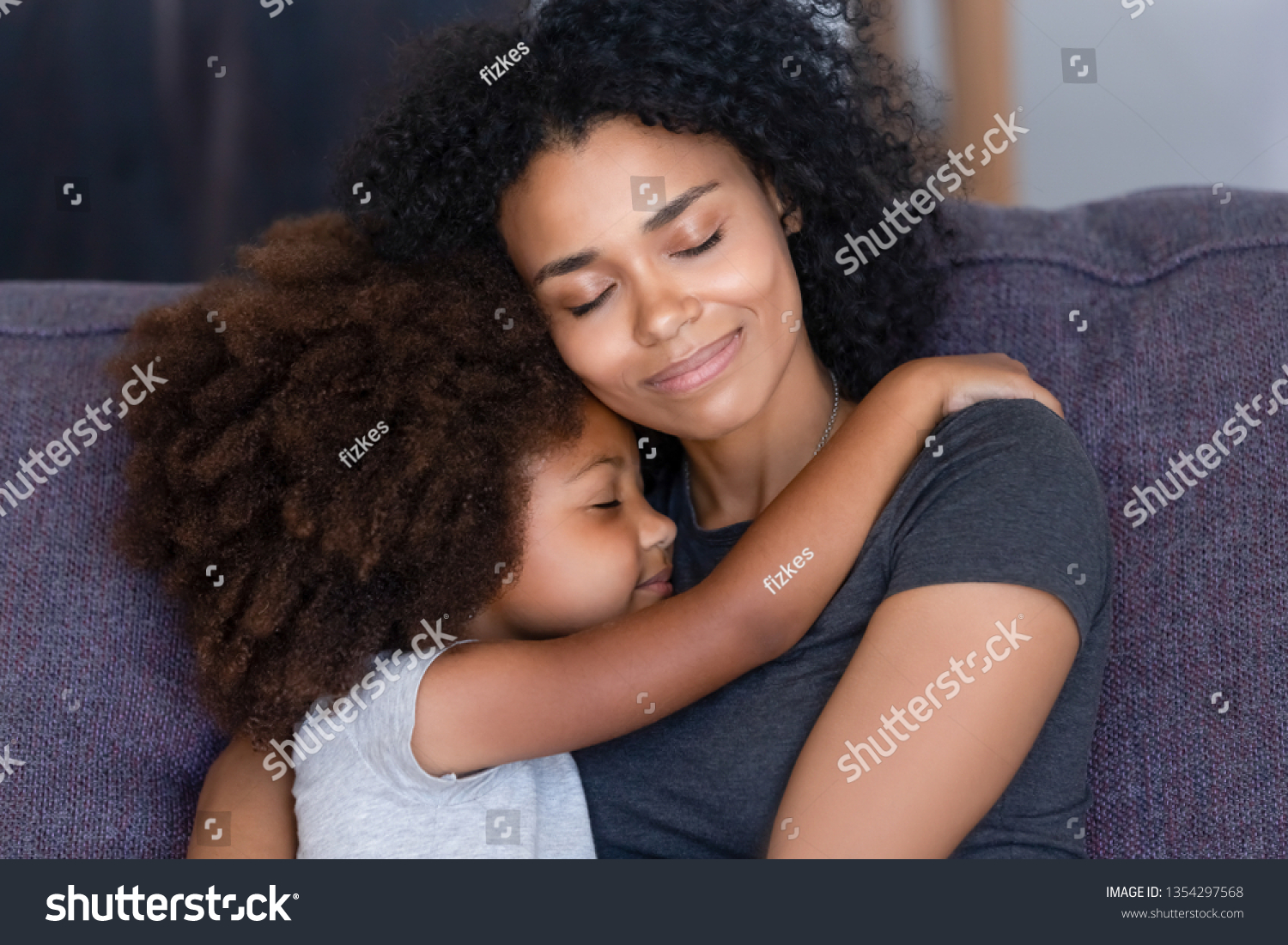 Close up biracial family portrait loving mother and little daughter sitting on couch at home hugging with closed eyes. Love, new mom for adopted child, warm relationships, caring elder sister concept #1354297568