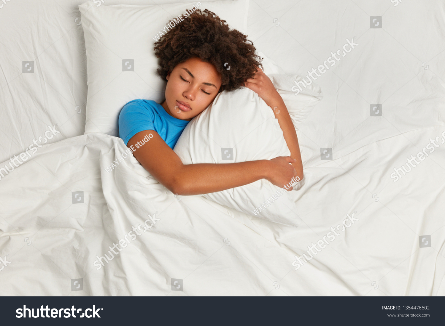 Dark skinned restful woman lying in bed and sleeps peacefully, hugs pillow, enjoys comfort and softness of bedclothes, wears blue t shirt, has healthy sleep at night. Good rest and bed time. #1354476602