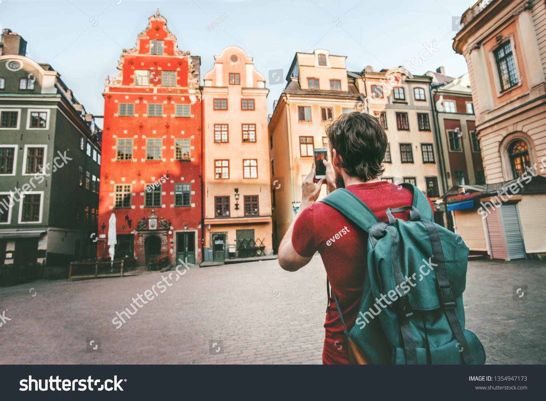 Man tourist sightseeing Stockholm city Gamla Stan landmarks traveling lifestyle girl taking photo by smartphone Europe trip summer vacations  #1354947173