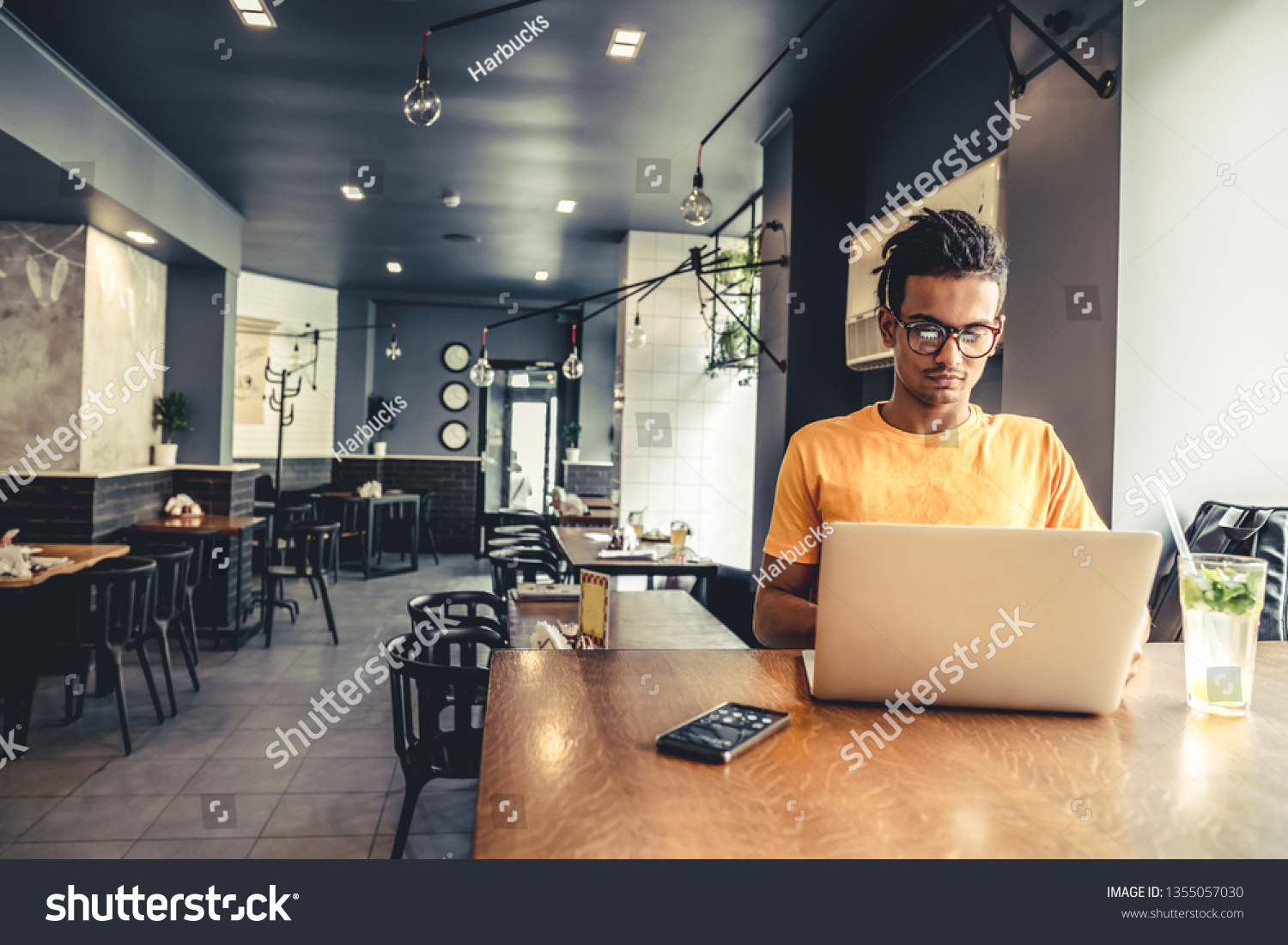 Handsome and successful indian man freelancer work laptop in cafe. Freelance and remote work. #1355057030