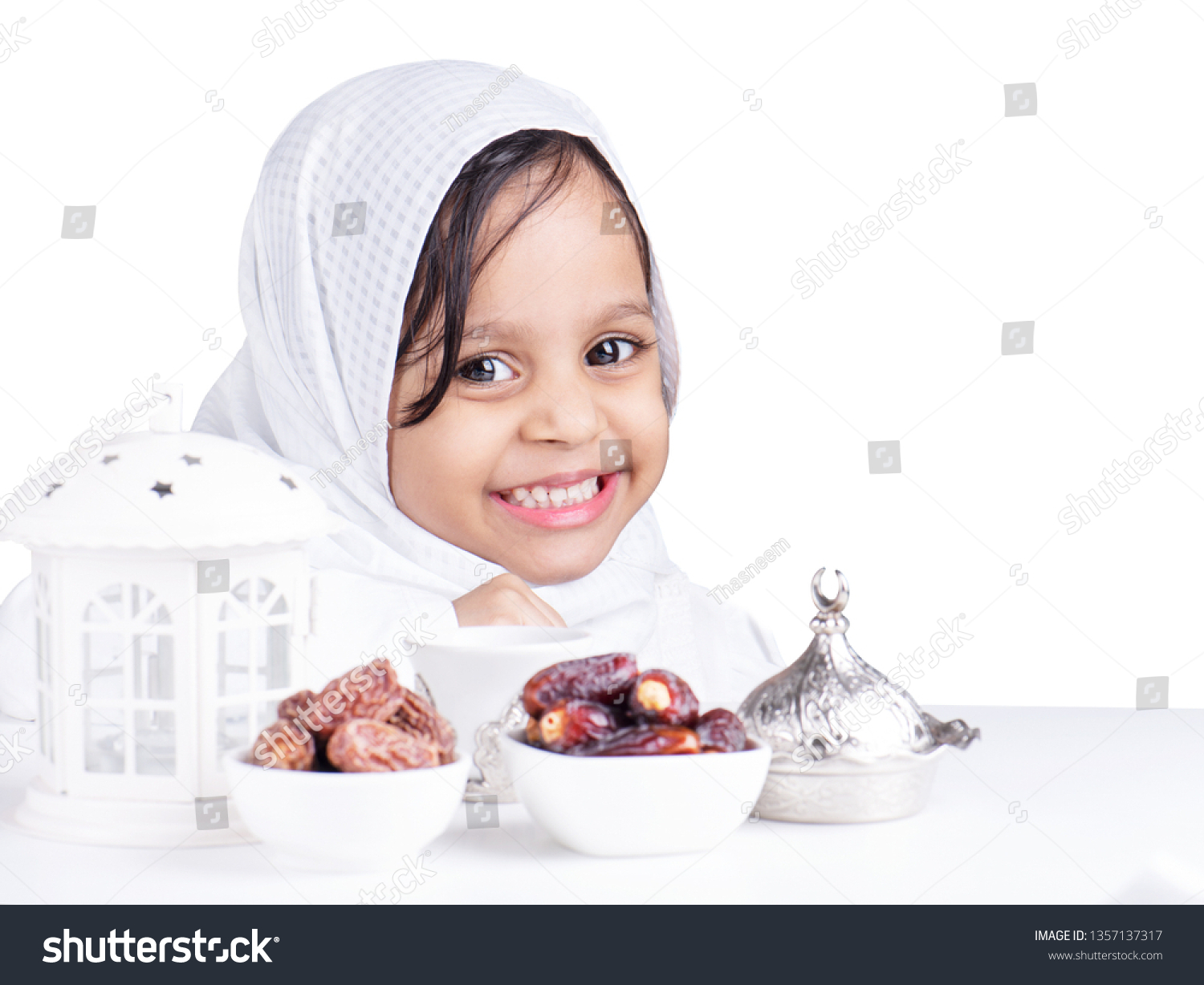 Ramadan background with cute muslim girl in front of dates fruits and lantern