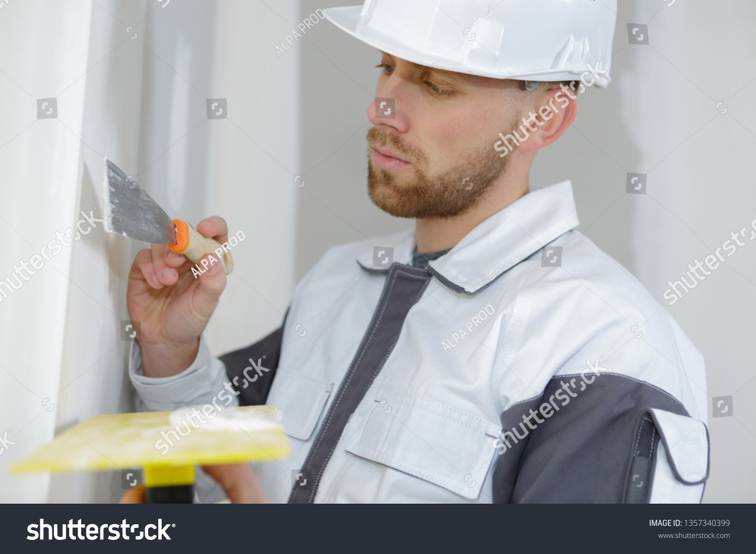construction worker plasterer with trowel plastering a wall #1357340399