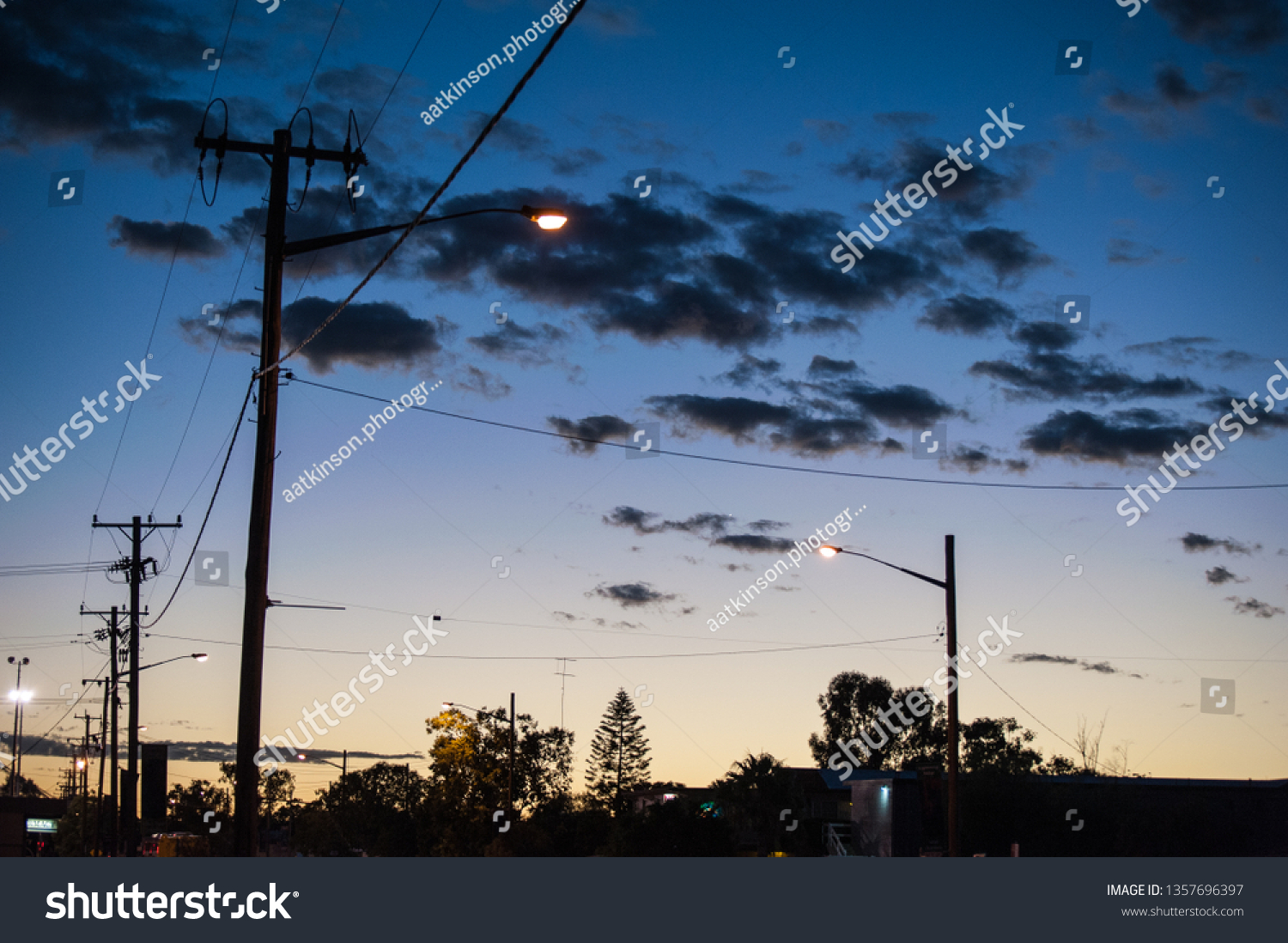 Sunrise in the town of Lightning Ridge creating silhouttes of the street lights, poles and power lines #1357696397