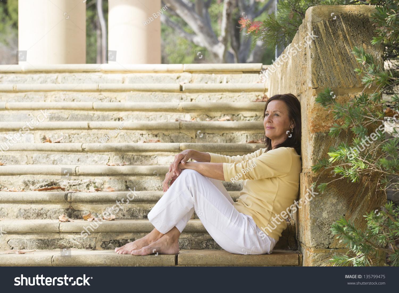 portrait confident attractive mature woman sitting stock photo