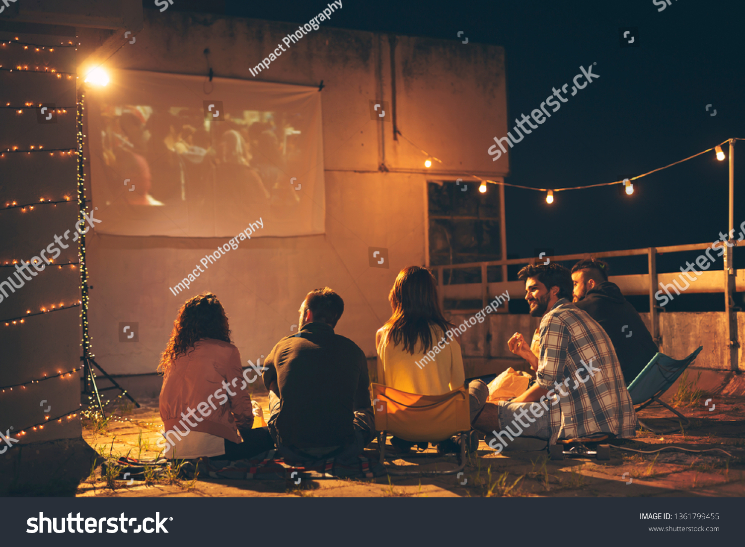 Group of young friends watching a movie on a building rooftop terrace, eating popcorn, drinking beer and having fun #1361799455