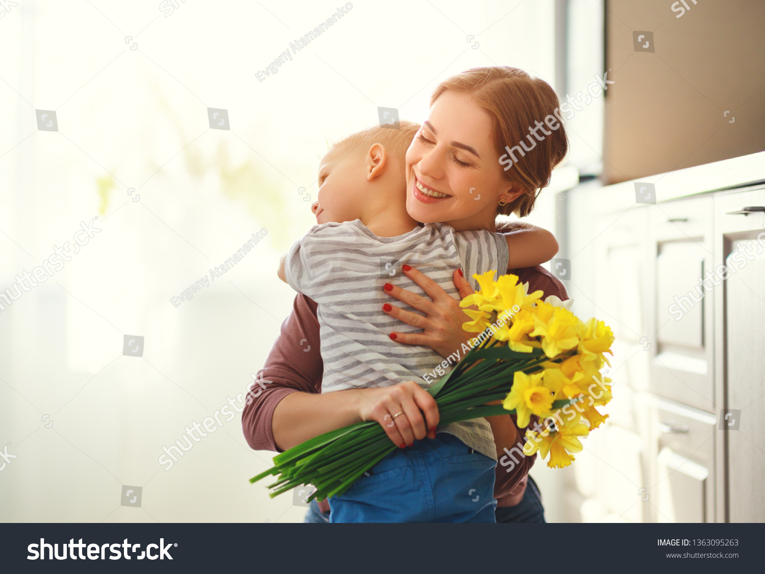 happy mother's day! child son congratulates mother on holiday and gives flowers