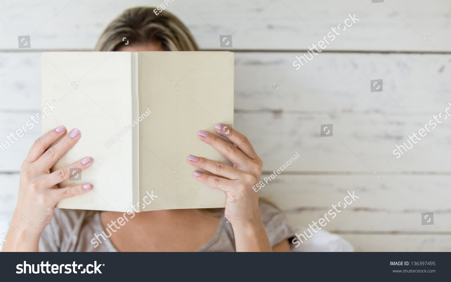 Book Covering Face : Woman reading book covering her face stock photo