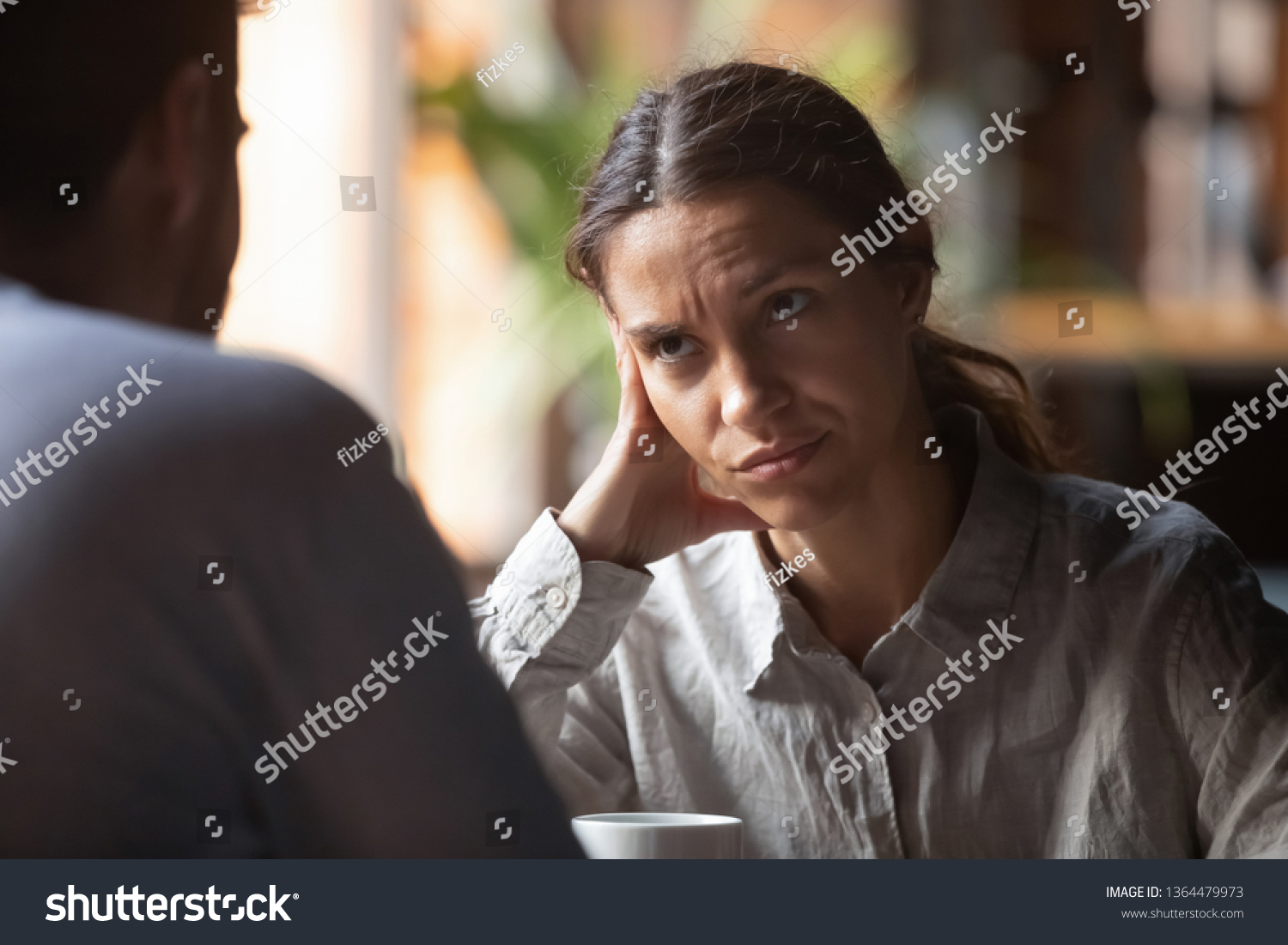 Focus on mixed race irritated young female sitting in cafeteria on speed dating with boring male rear view. Unsuccessful unlucky romantic date failure, bad first impression and poor companion concept #1364479973
