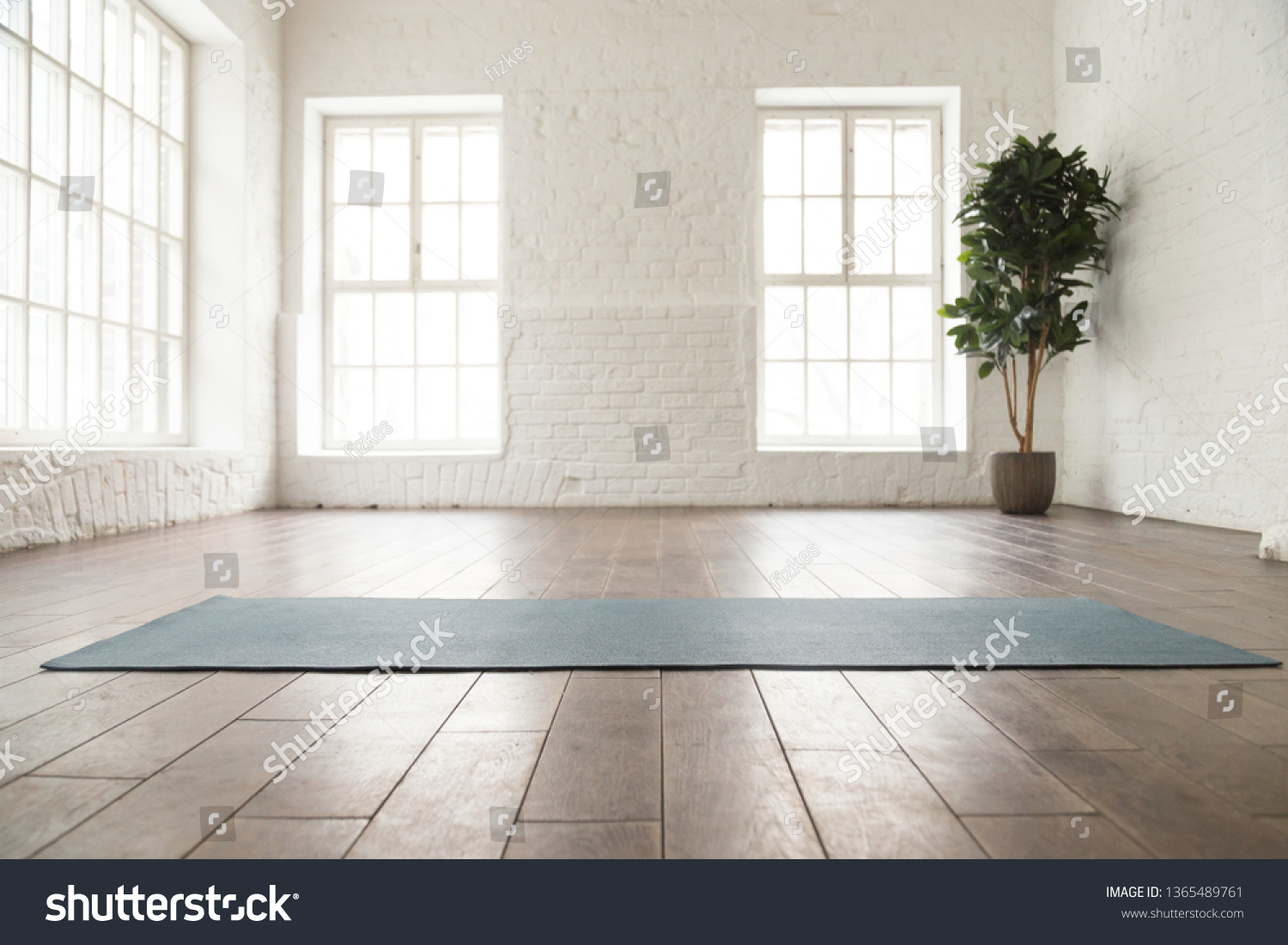 Unrolled yoga mat on wooden floor in modern fitness center or at home with big windows and white brick walls, comfortable space for doing sport exercises, meditating, yoga equipment #1365489761