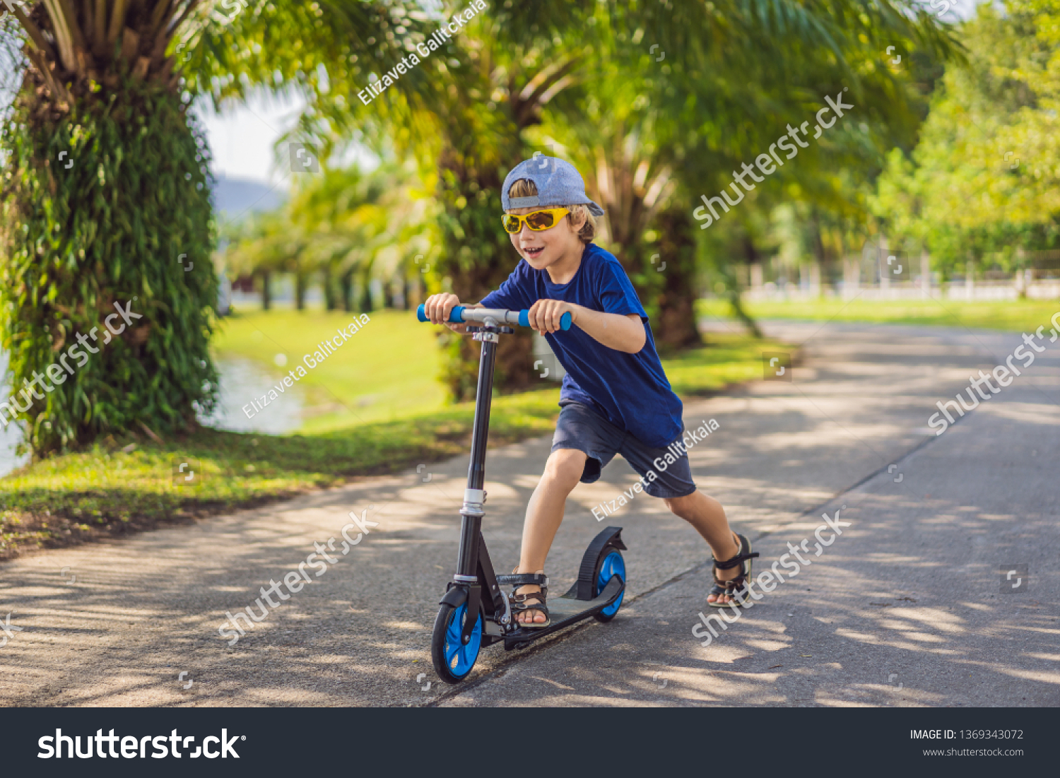 Child on kick scooter in park. Kids learn to skate roller board. Little boy skating on sunny summer day. Outdoor activity for children on safe residential street. Active sport for preschool kid #1369343072