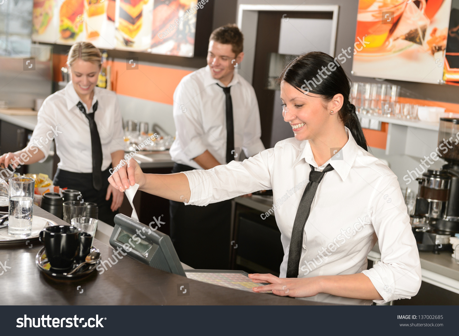 female cashier giving receipt colleagues working stock photo