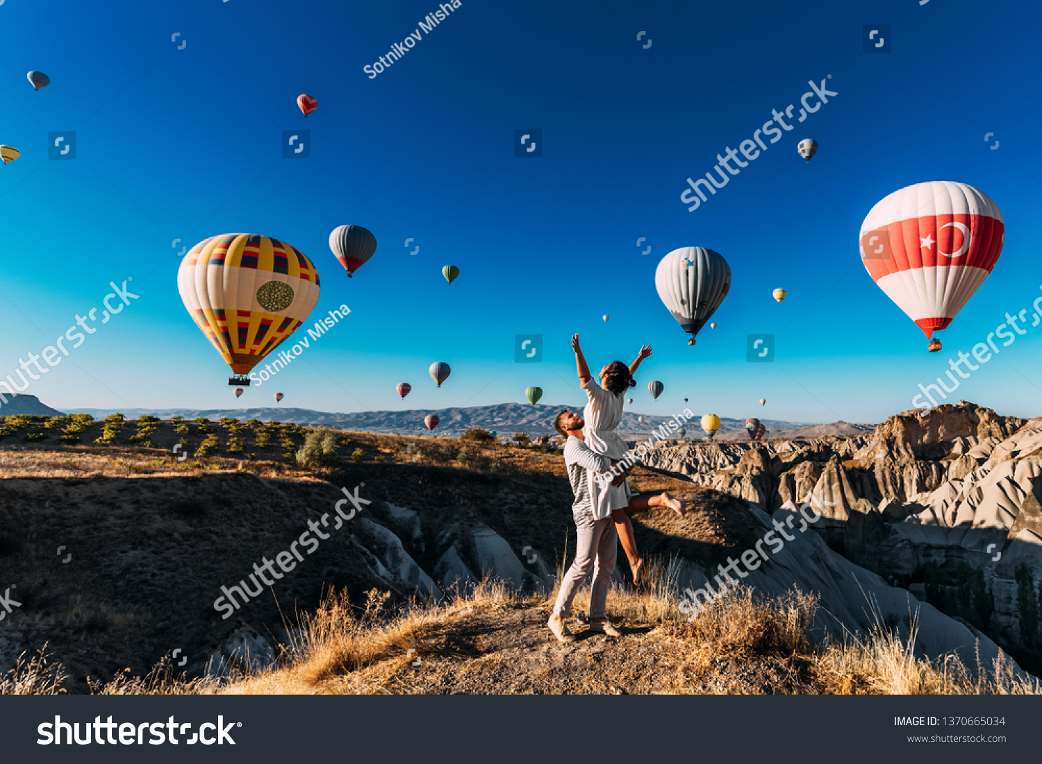 Wedding travel. Honeymoon trip. Couple in love among balloons. A guy proposes to a girl. Couple in love in Cappadocia. Couple in Turkey.  Man and woman traveling. Festival of balloons. Tourists #1370665034