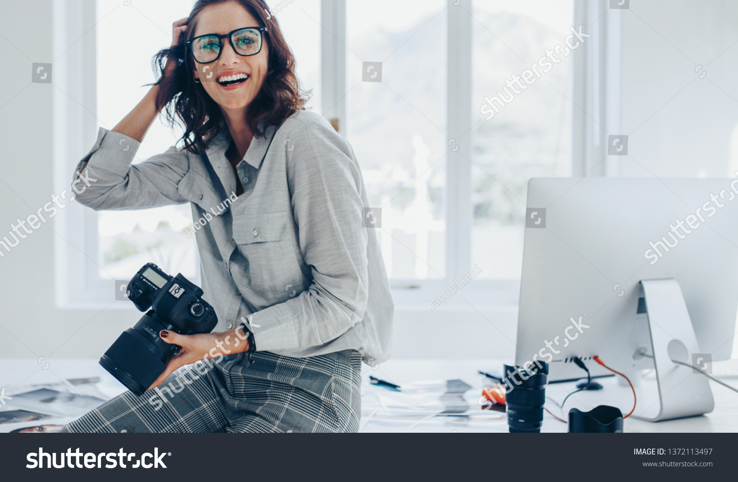 Smiling female photographer with a professional camera sitting on her desk. Woman with dslr camera in office looking away and smiling. #1372113497