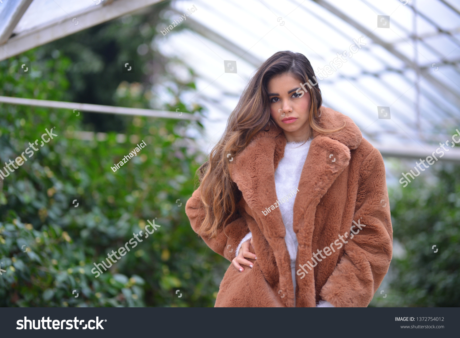 posing girl with brown fur in front of the mansion and greenhouse #1372754012