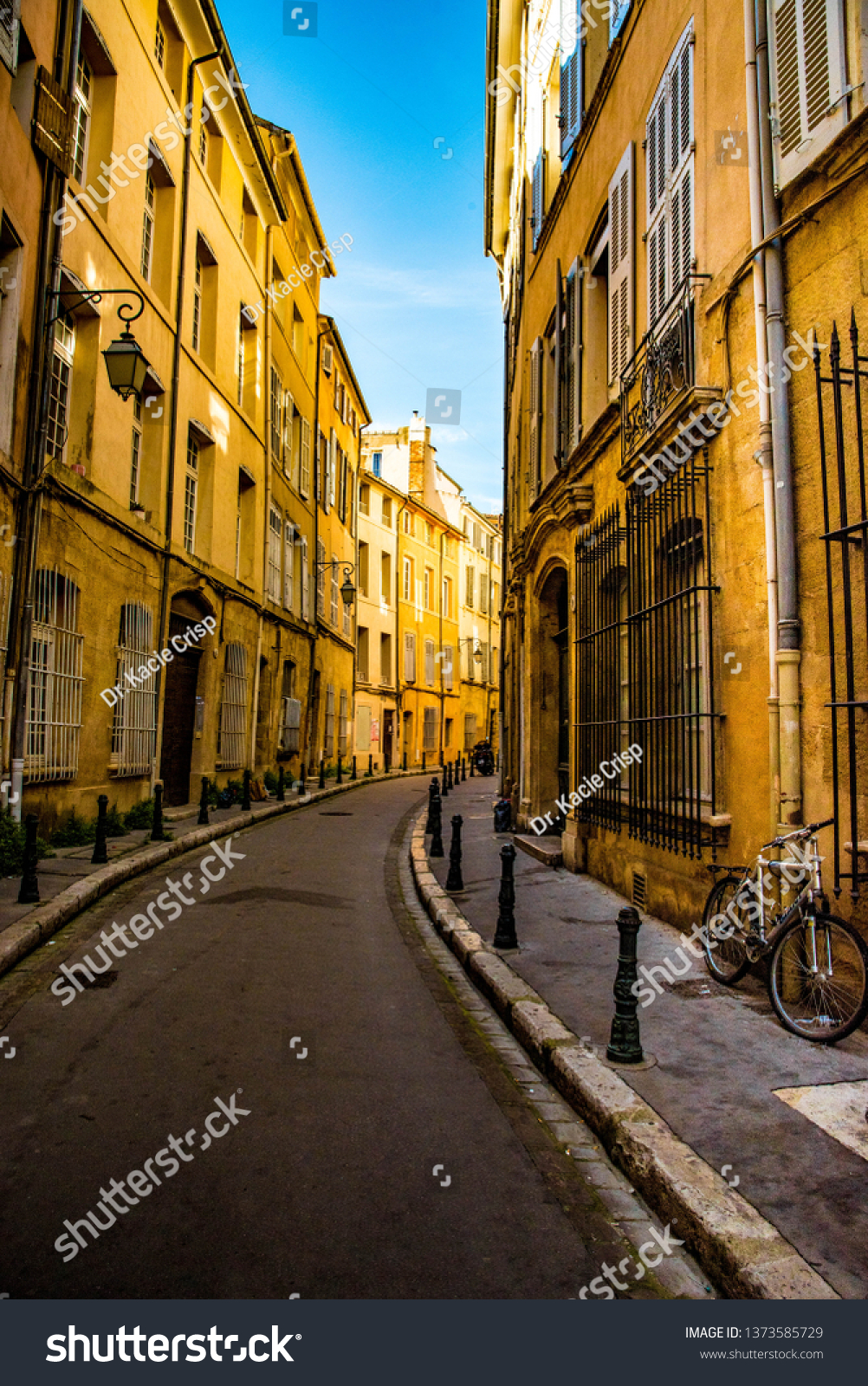 Stone Aix En Provence bicycle rests against honey colored stone stock photo (edit