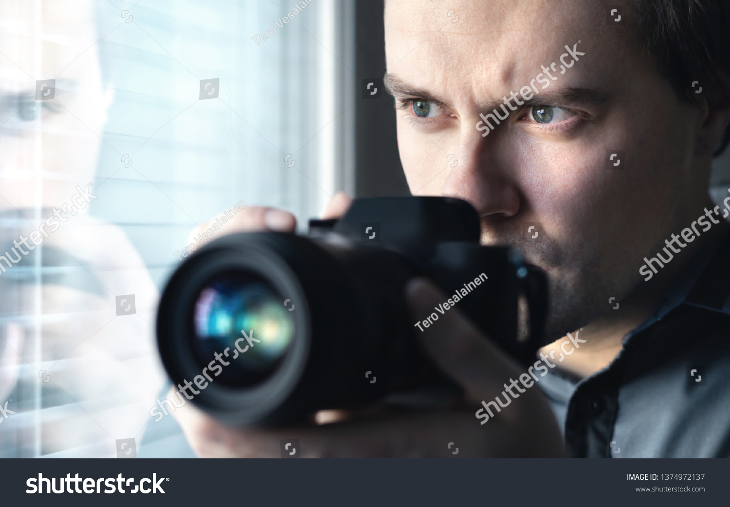 Private detective, undercover cop, investigator, spy or paparazzi with camera taking photos. Agent or police spying, investigating or following people. Espionage or surveillance concept. Man hiding. #1374972137