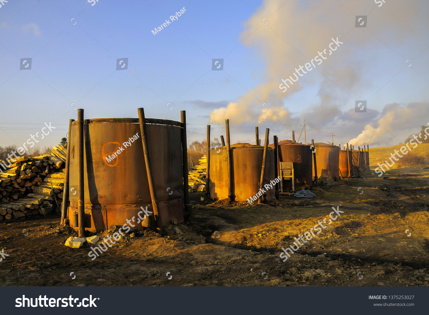 Several smoking charcoal kilns with burning wood. The Charcoal Kiln is a piece of equipment used to burn Wood into Coal. South Poland.