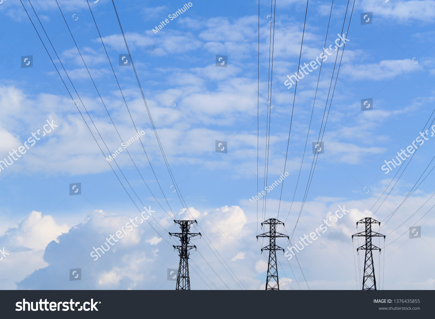 Three transmission towers before a blue cloudy sky. Cables of pwer towers over the sky. Electricity pylon wires coming from the electric pylons situated on the background. #1376435855