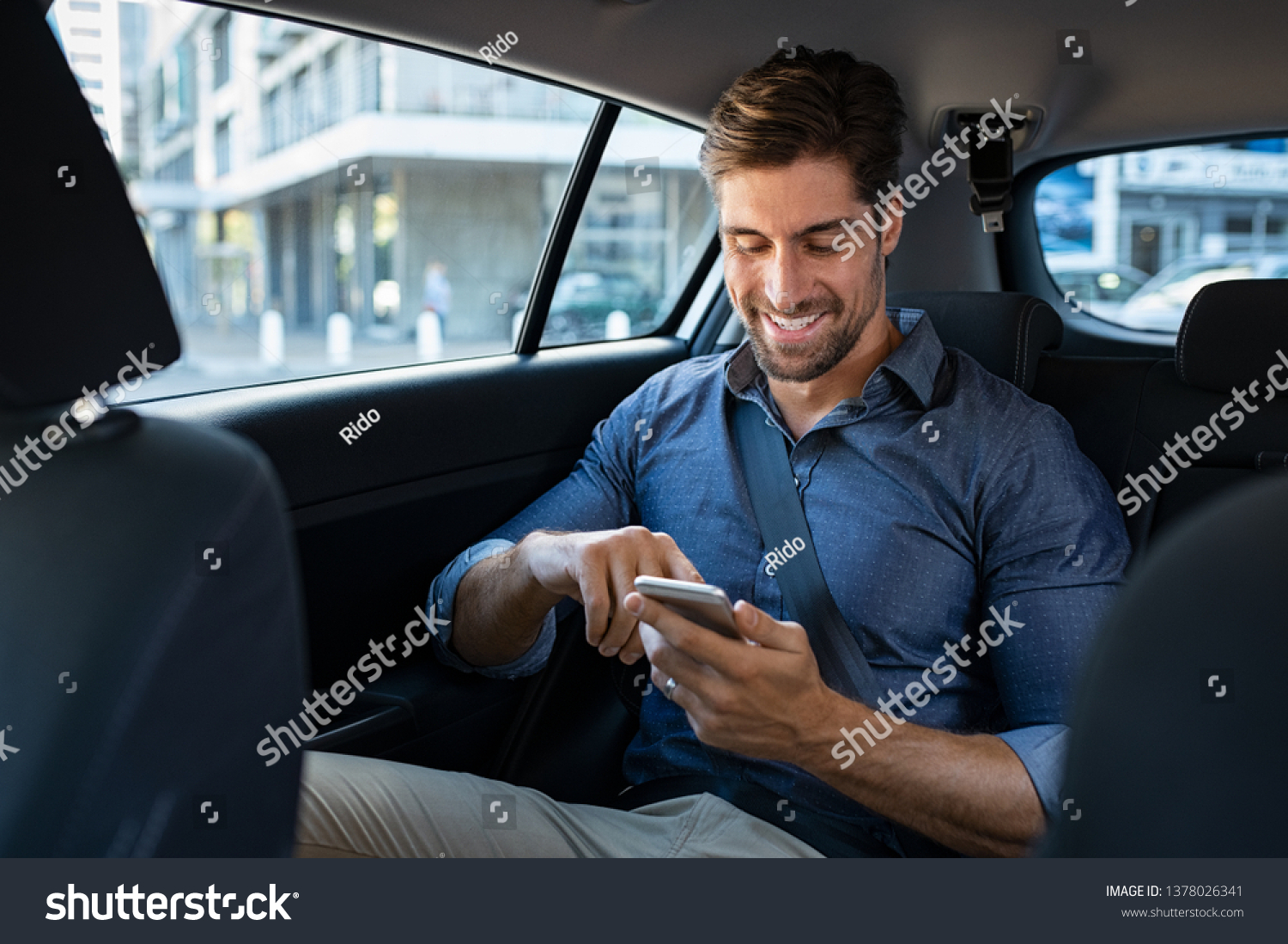 Happy smiling business man typing message on phone while sitting in a taxi. Young businessman in formal clothing using smartphone while sitting on back seat in car. Cheerful guy messaging with cell. #1378026341