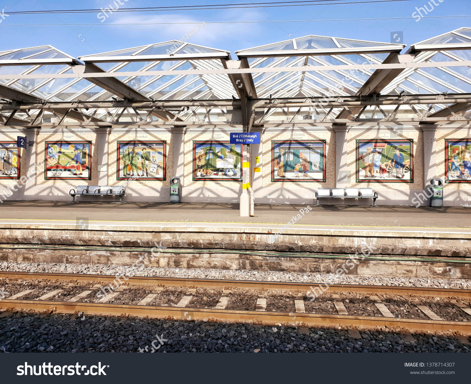 BRAY, CO. WICKLOW, IRELAND - APRIL 21, 2019: Empty platform at the Bray (Daly) train station on sunny day.  Historical mosaics on the wall. Glass roof gives shadows. A view from the opposite platform.