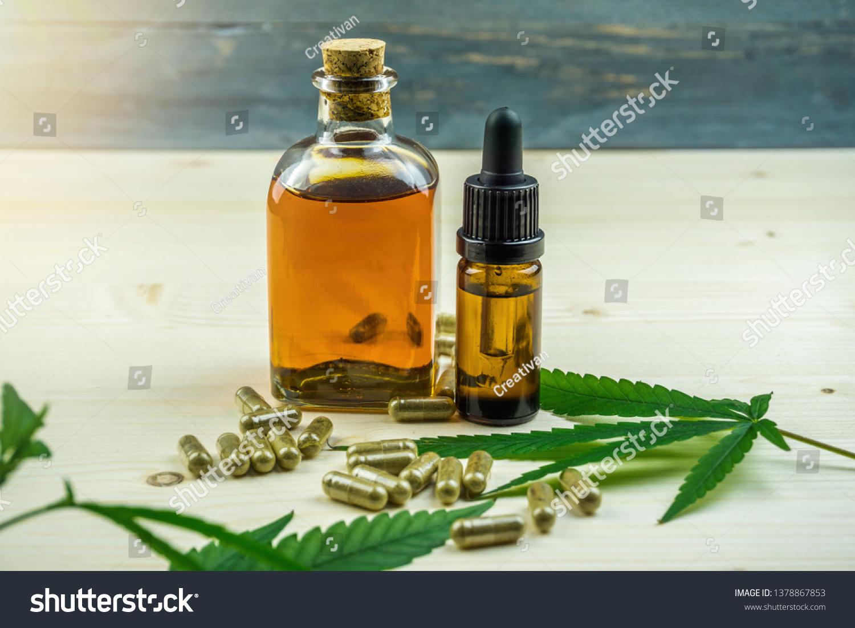 Clear CBD Cannabidiol capsules and cannabis oil on wooden backdrop #1378867853
