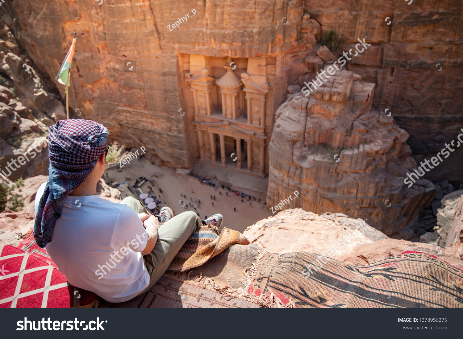 Asian man traveler sitting on carpet viewpoint in Petra ancient city looking at the Treasury or Al-khazneh, famous travel destination of Jordan and one of seven wonders. UNESCO World Heritage site. #1378956275