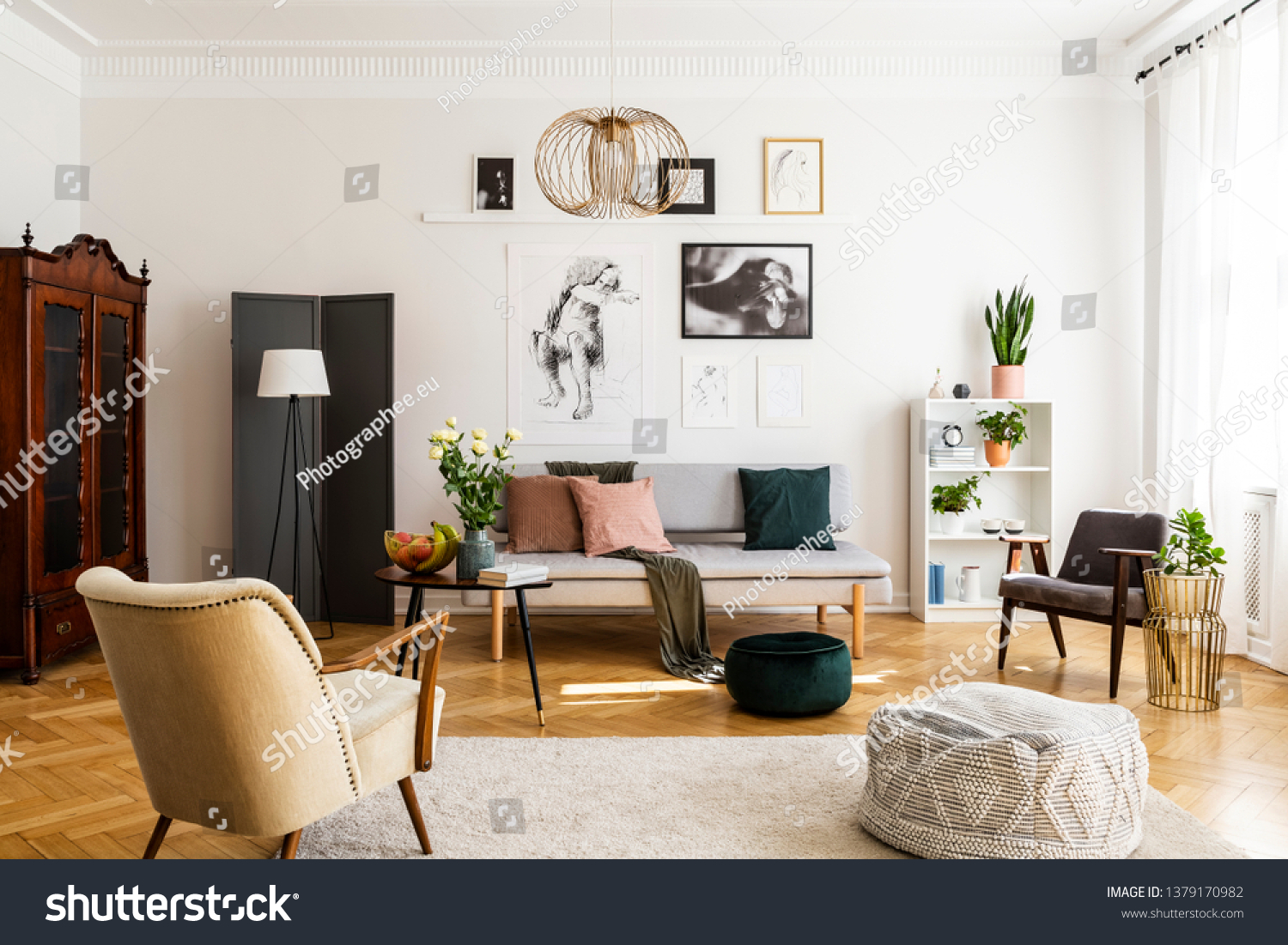 Stylish beige armchair and pouf on the cozy carpet in classy living room interior with grey settee and vintage furniture #1379170982
