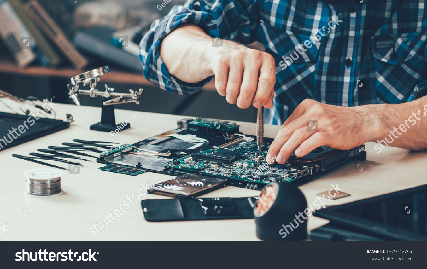 Computer repair shop. Engineer performing laptop maintenance. Hardware developer fixing electronic components. PC technology