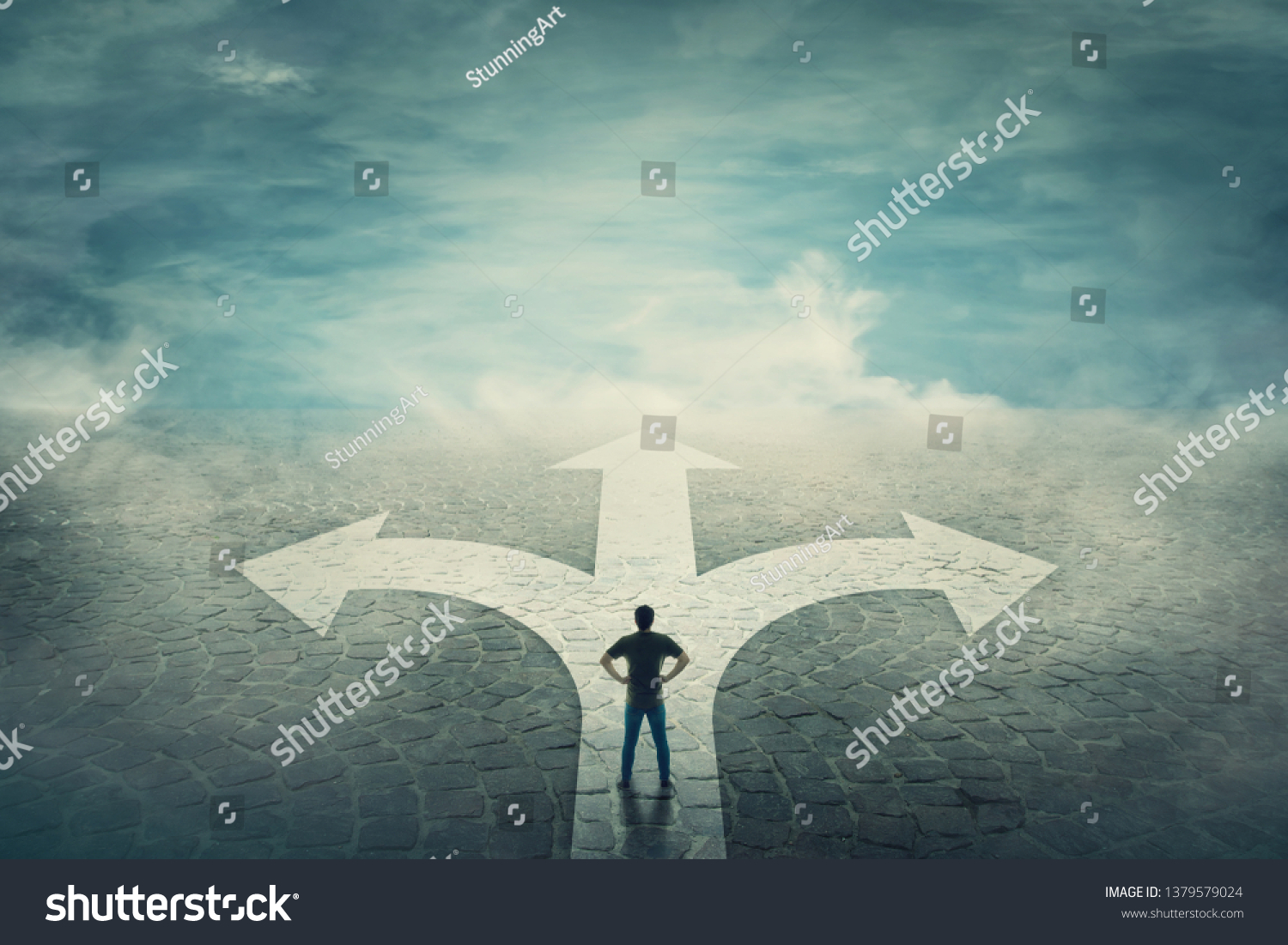 Confident man, hands on hips, stands in front of a crossroad with road split in three different ways as arrows. Choosing the correct pathway between left, right and front. Difficult decision concept. #1379579024