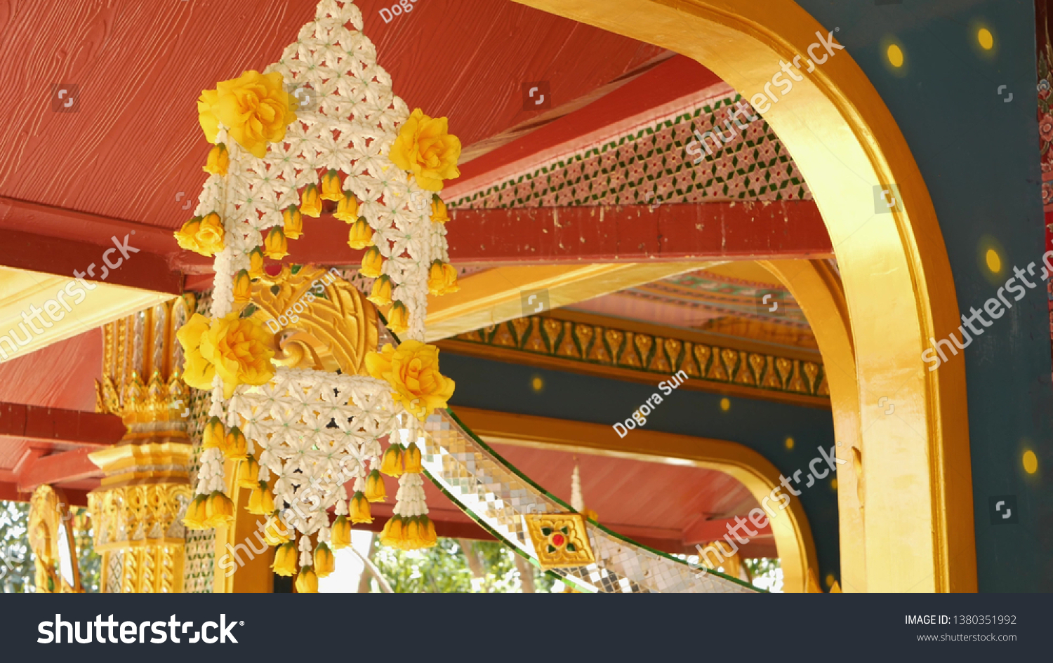 Floral interior decorations of oriental building. Beautiful flower compositions hanging on ceiling of ornamental building of buddist temple on sunny day in Thailand. #1380351992