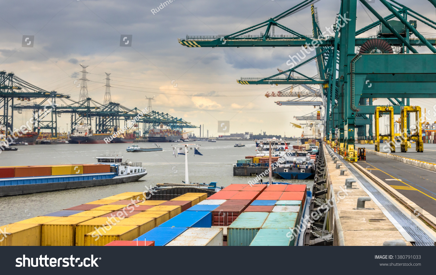 Loaded ships in busy port of Antwerp at container terminal with automated cranes and lots of vessels. Belgium #1380791033