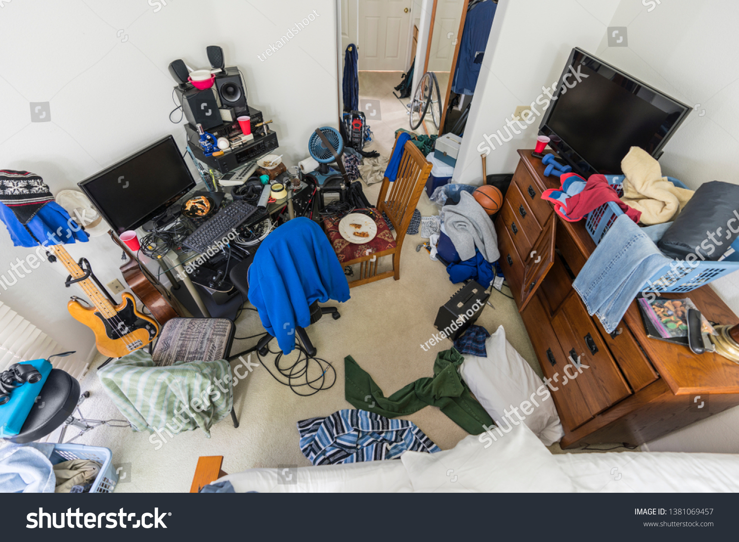 Very messy, cluttered suburban teenage boys bedroom with piles of clothes, music and sports equipment.   #1381069457