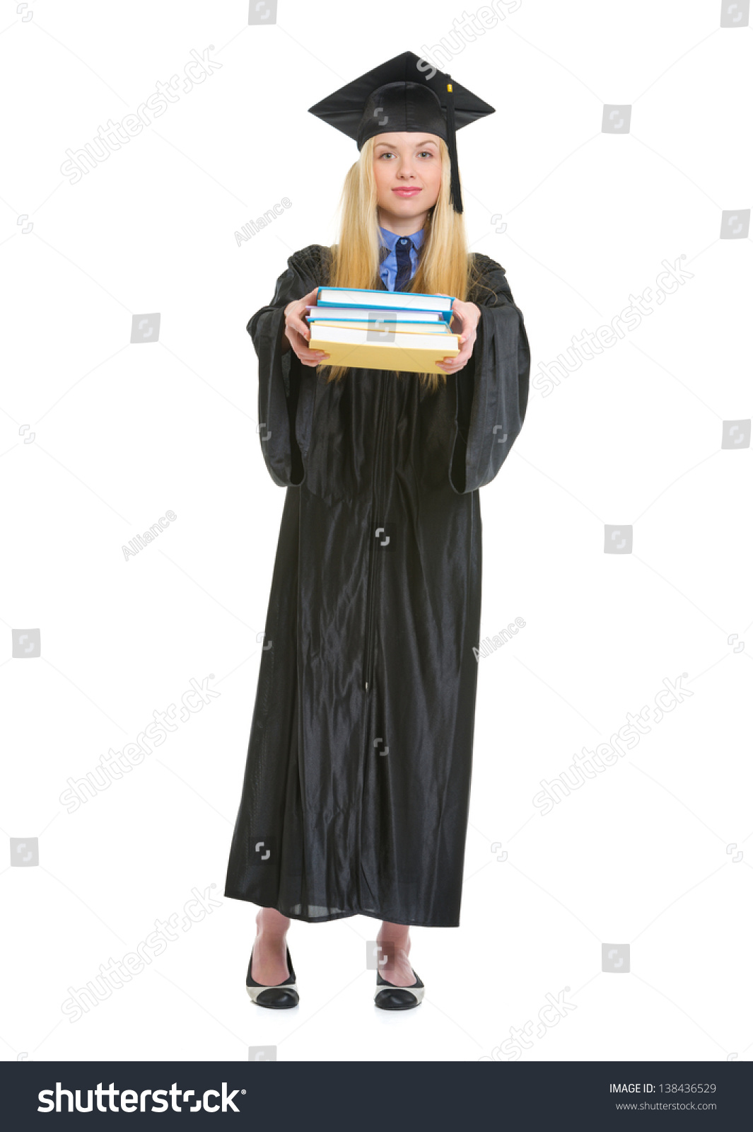 Full length portrait of young woman in graduation gown showing ...