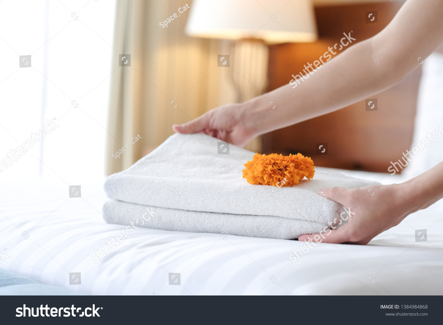 Hands of hotel maid bringing fresh towels to the room #1384984868