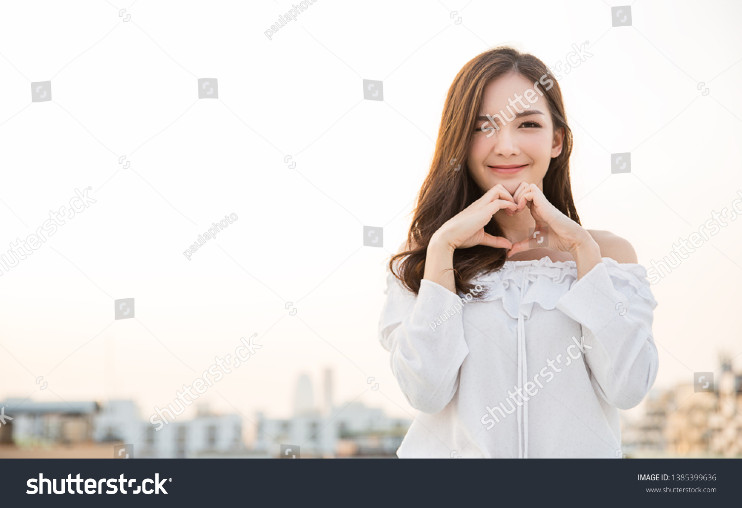 Portrait of young beautiful asian woman hands gesture in heart shape on city sky roof top. Smile face asian lady girl wear casual cloth. Japanese girl lifestyle, lovely woman valentines' day concept  #1385399636