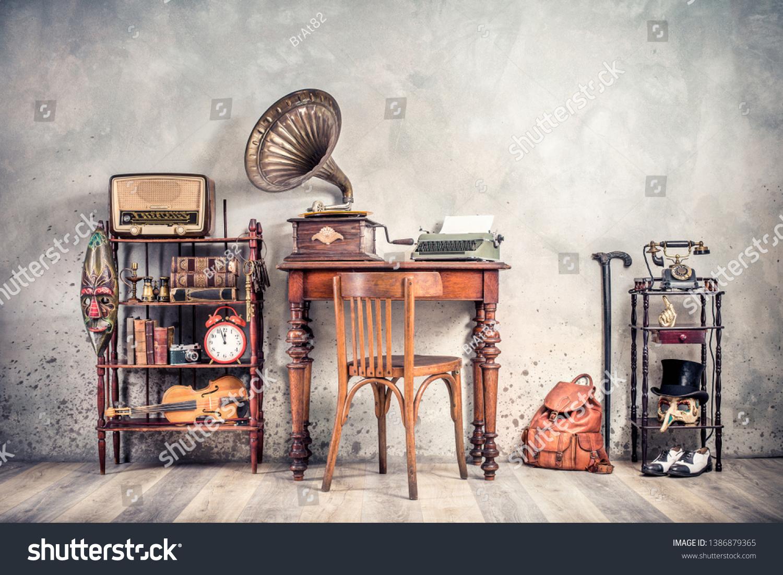 Antique chair, old typewriter, retro radio,  gramophone on wooden desk, books, clock, camera, binoculars, fiddle, keys on shelf, mask, cylinder hat, shoes, cane, backpack. Vintage style filtered photo #1386879365