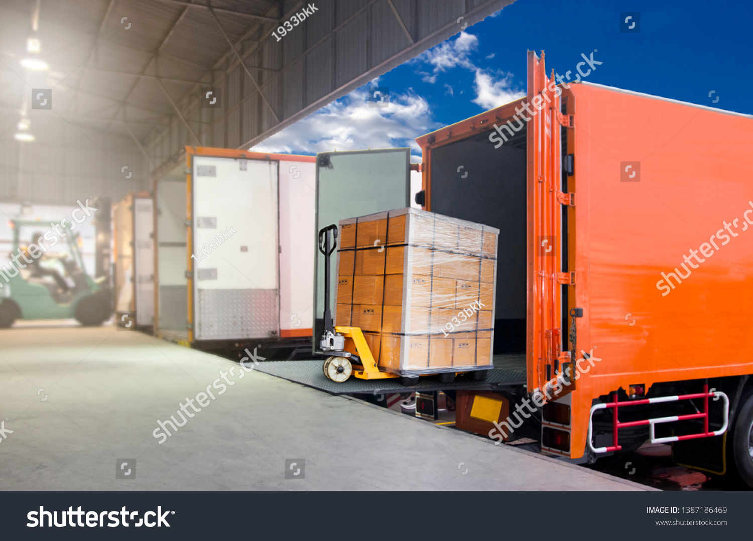 Distribution warehouse and Logistics, freight industry transport by truck. Forklift loading cargo into a truck, trucks docking at warehouse #1387186469