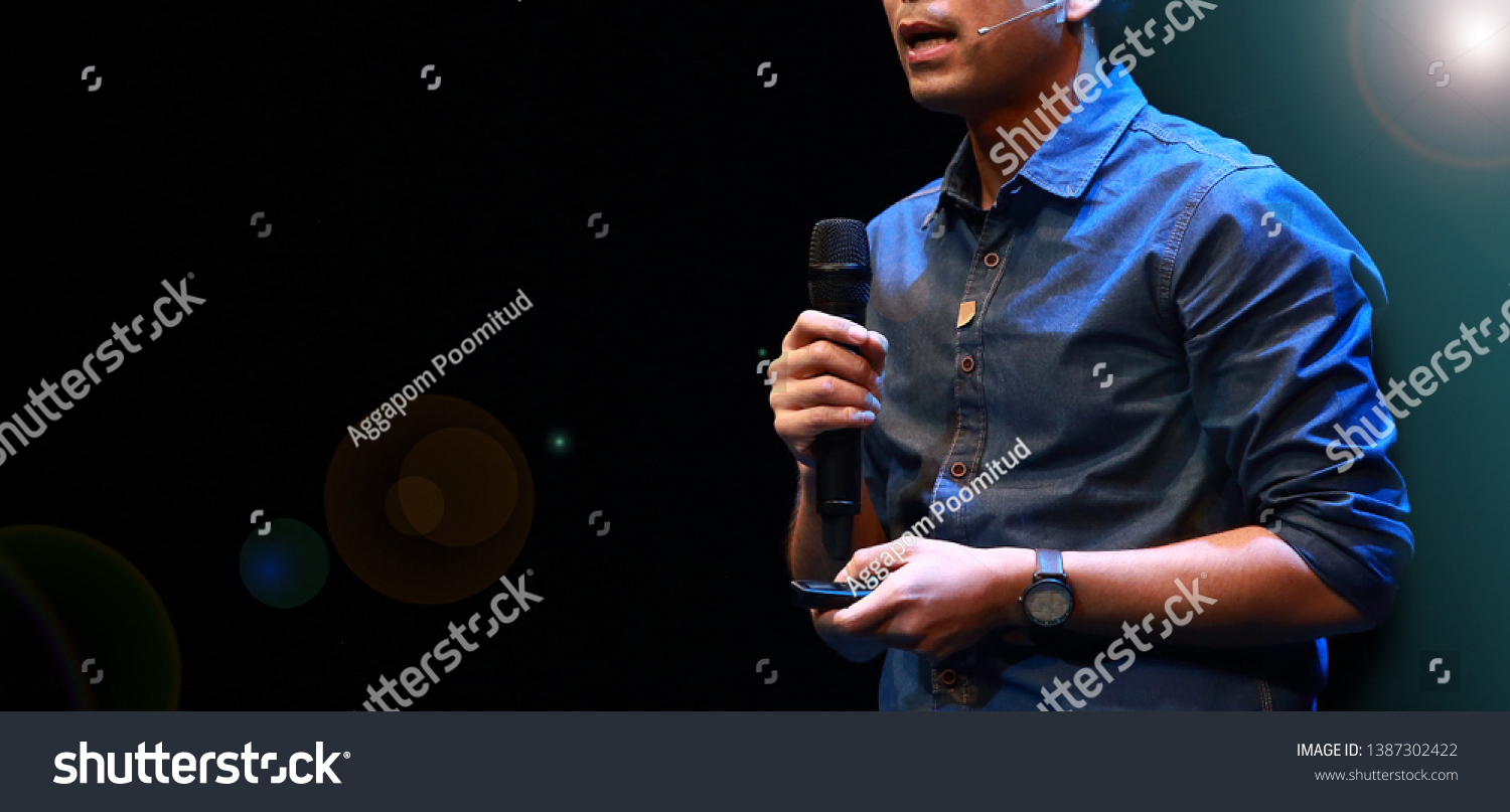 The male speaker is doing the public speaking with the dark background under the spot light and lense flare, in concept of talk show, flare light, motivational speaking, inspiration speaker. #1387302422