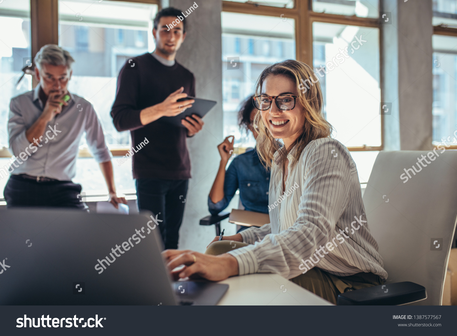 Female entrepreneur working on laptop and explaining strategy to attract followers to online web store while having meeting with colleagues in office. #1387577567